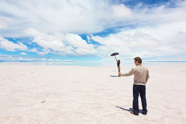 Ilusión óptica de un hombre y una mujer en la playa