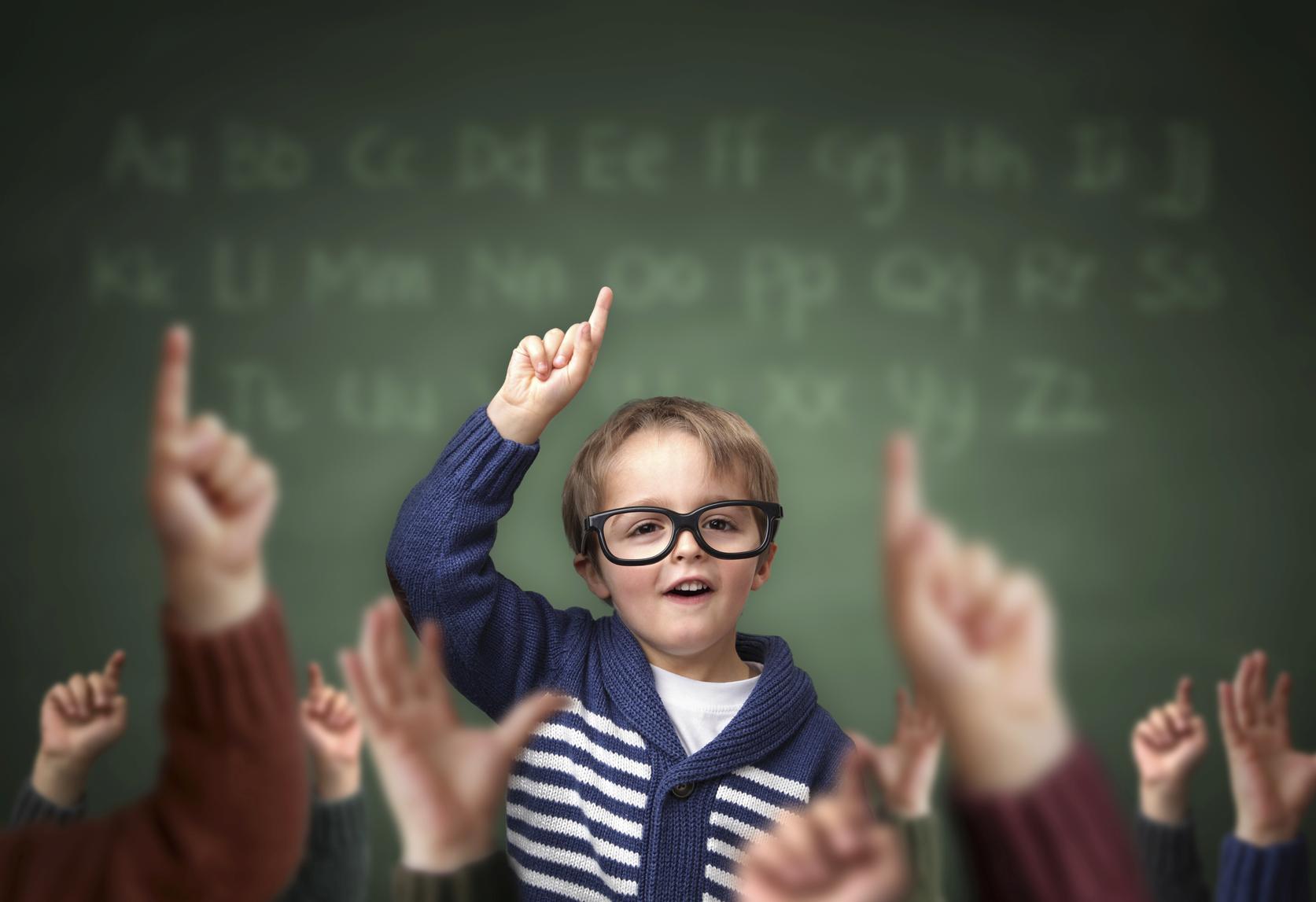 Niño con gafas frente a una pizarra señala hacia arriba