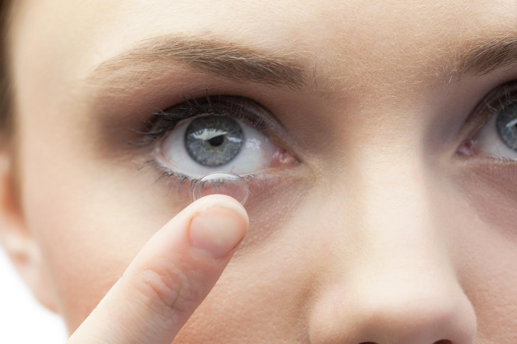 Mujer de ojos azules poniéndose una lente de contacto