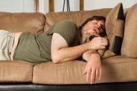 Hombre con camiseta verde durmiendo en sillón marrón