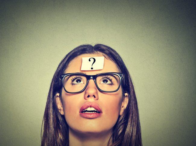 Mujer con gafas negras mirando una interrogación
