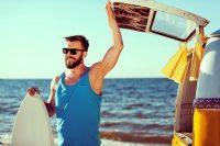 Hombre con gafas de sol guarda tabla de surf en camioneta