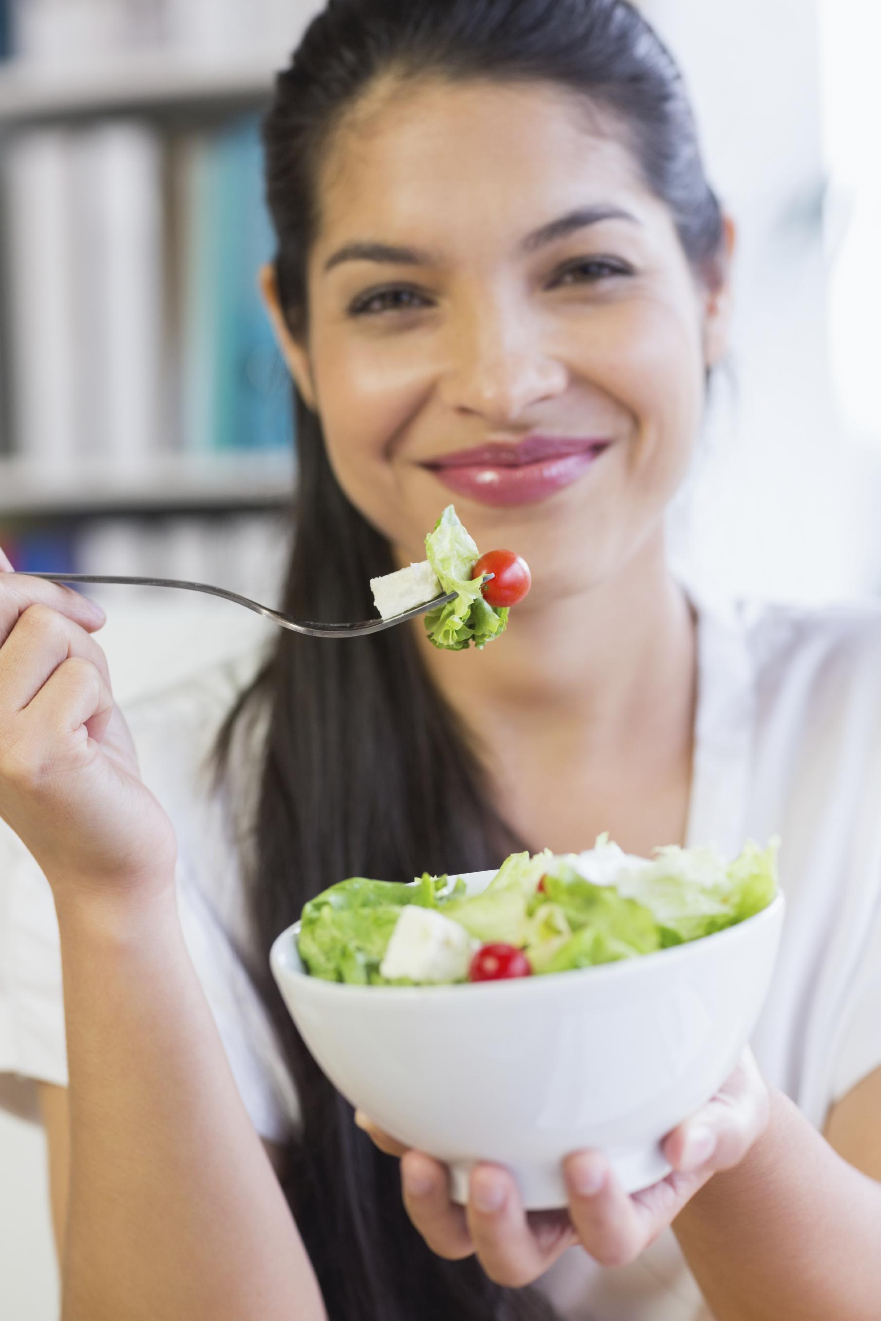 Mujer morena comiéndose una ensalada