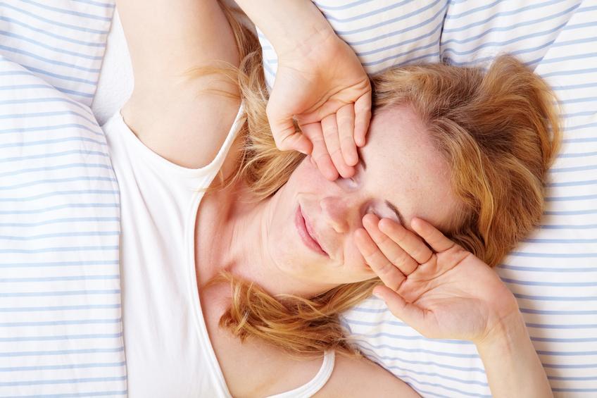 Mujer rubia se frota los ojos en la cama