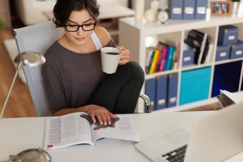 Mujer morena lee una revista llevando gafas mientras toma un café