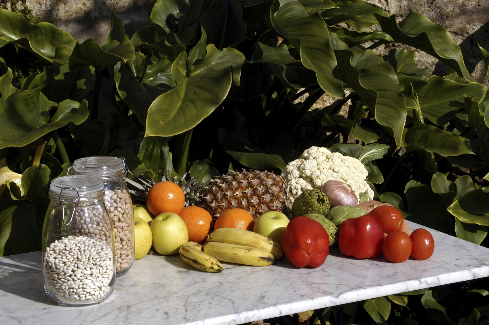 Legumbres, hortalizas y frutas sobre una mesa blanca