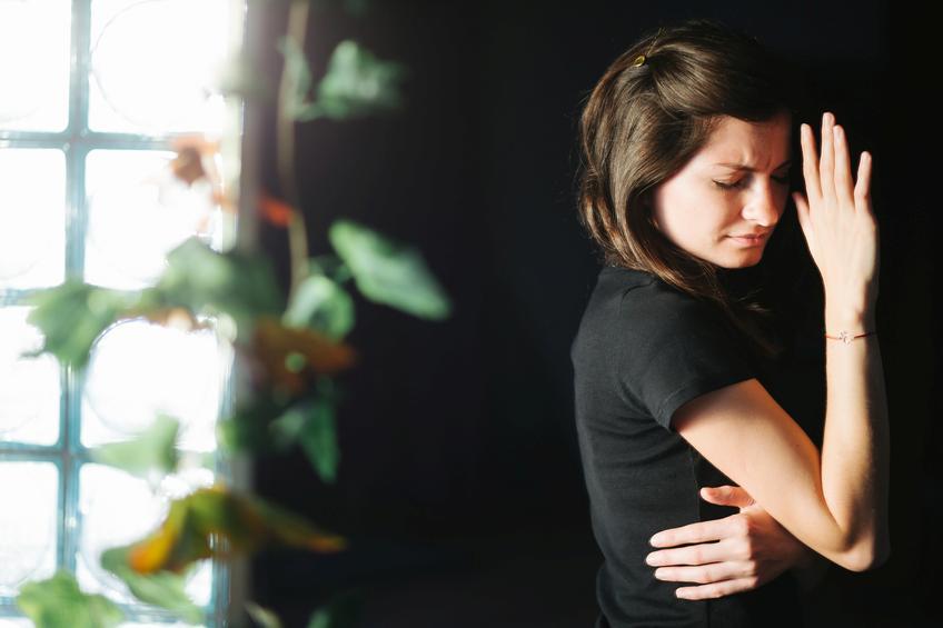 Mujer morena con camiseta negra apoyada en pared negra
