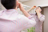 Hombre con camisa rosa echándose gotas frente al espejo