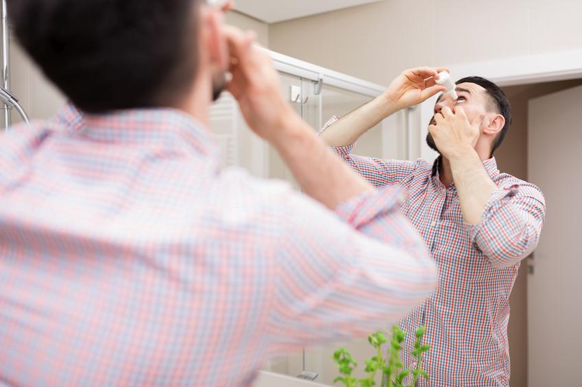 Hombre echándose un colirio frente a un espejo