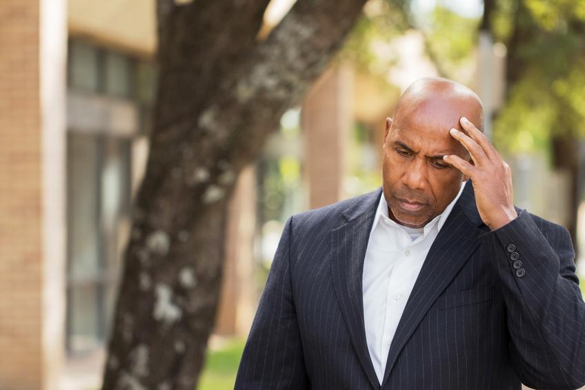 Hombre con chaqueta a rayas tocándose la cabeza