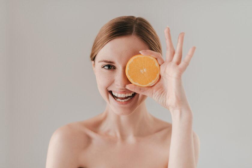 Chica con el pelo recogido se pone una naranja en un ojo