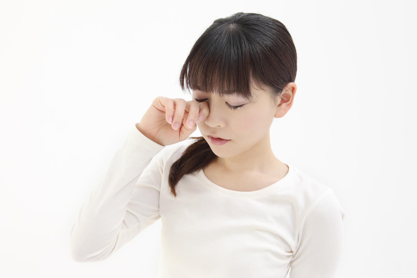 Niña morena con camiseta blanca se frota un ojo