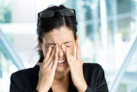 Mujer morena con gafas en la cabeza se frota los ojos