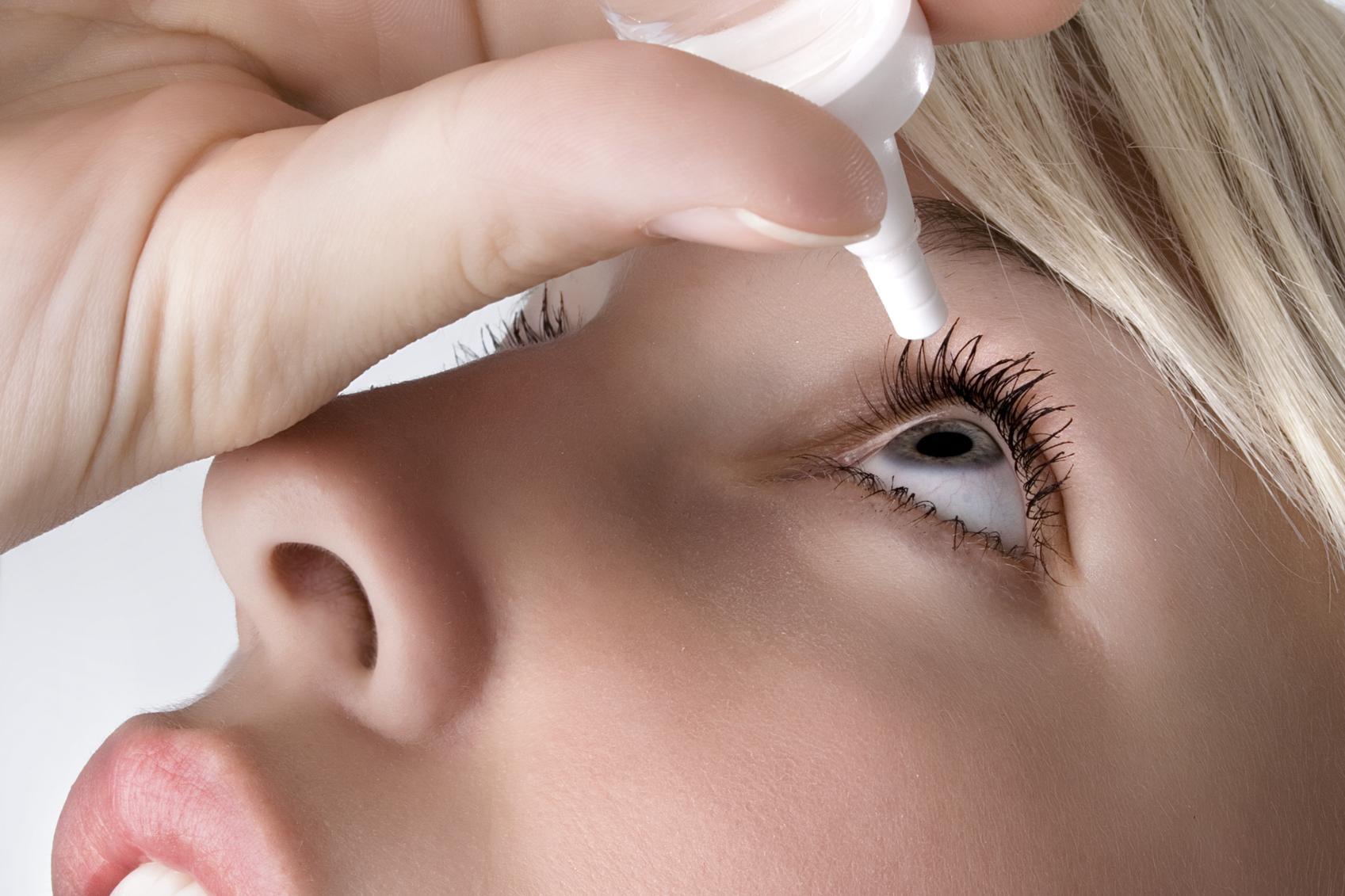 Mujer rubia echándose un colirio en el ojo