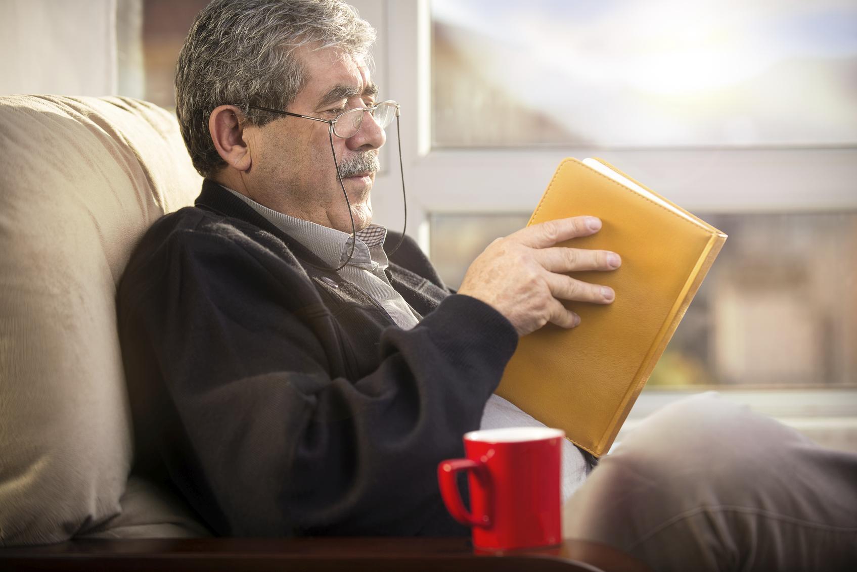 Hombre con gafas leyendo un libro amarillo