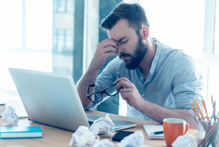 Hombre con barba se quita las gafas frente a ordenador portátil
