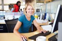 Mujer rubia con camiseta azul trabajando con ordenador en oficina