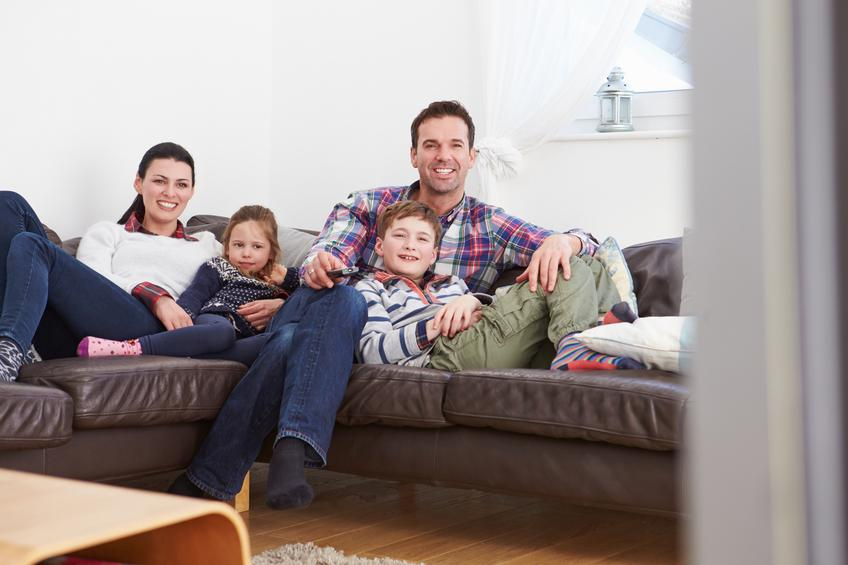 Familia con dos hijos tumbados en un sofá viendo la tv