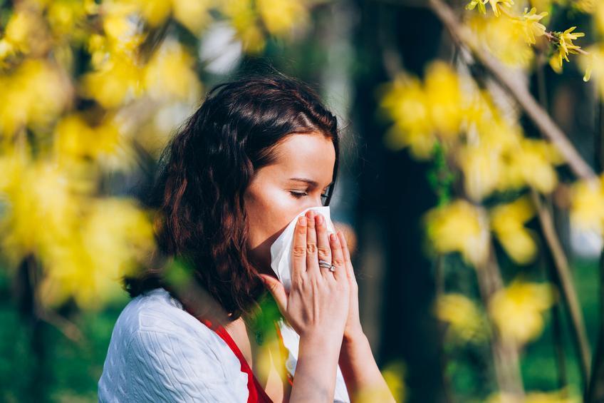 Mujer morena sonándose con un pañuelo blanco