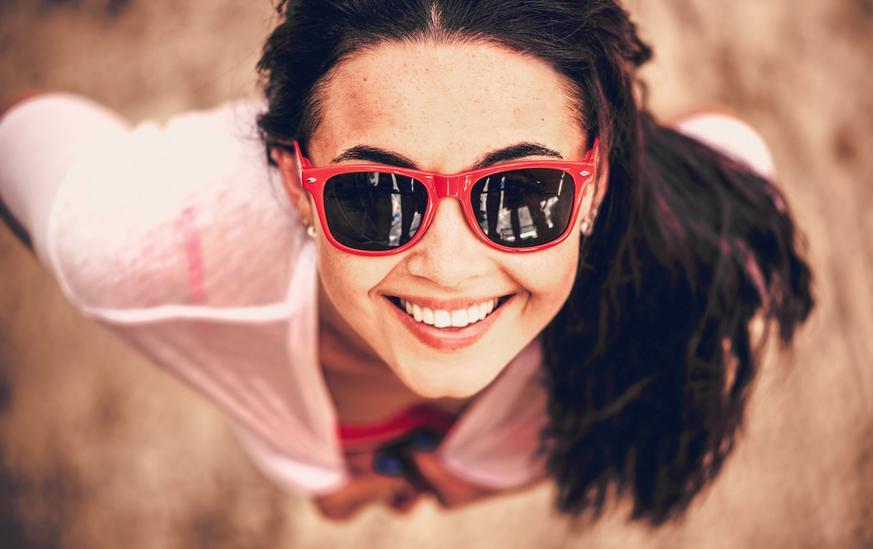 Mujer morena con gafas de sol rojas mirando hacia arriba