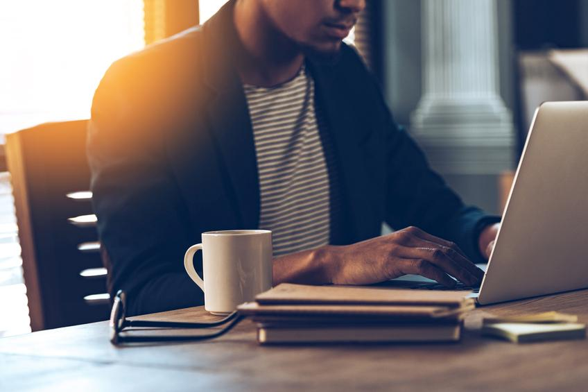 Hombre con chaqueta y camiseta a rayas trabajando frente a un portátil