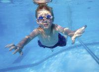 Niño buceando en piscina con gafas graduadas de natación
