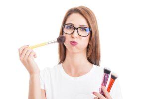Mujer con gafas maquillándose