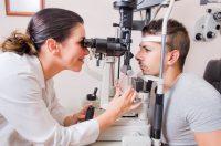 Oftamóloga con coleta revisando a paciente en consulta