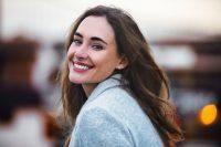 Mujer morena con abrigo gris mira atrás y sonríe