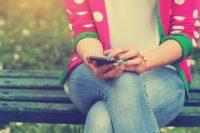 Mujer sentada en banco consultando el móvil