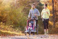 Pareja corriendo con bebé en carrito