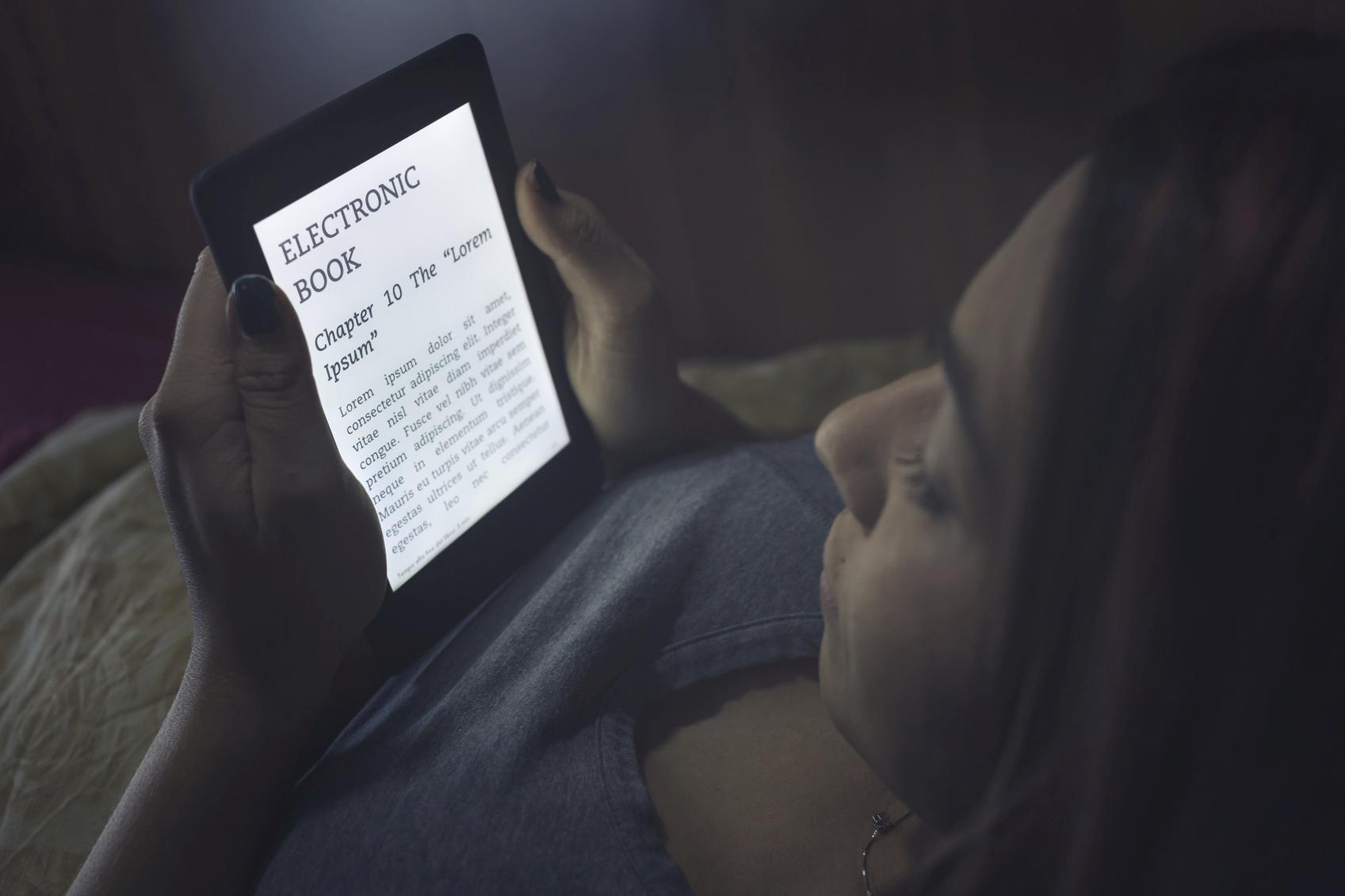 Mujer leyendo en un ebook en la oscuridad