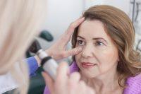 Mujer con chaqueta morada en revisión ocular