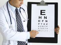 Oftalmólogo graduando vista a paciente con optotipo