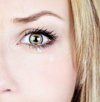 Mujer rubia con ojos verdes llorando