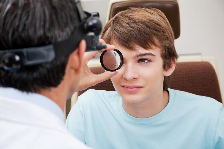 Niño con camiseta azul durante una revisión oftalmológica