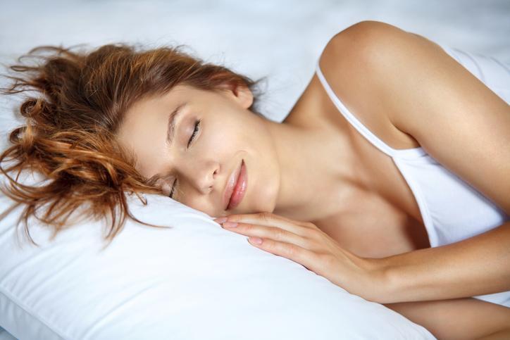 Mujer con camiseta blanca durmiendo en una cama