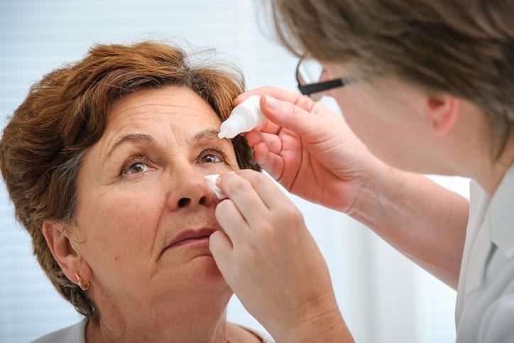 Mujer madura mientras le echan un colirio oftalmológico