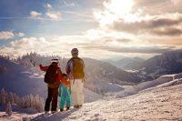 Pareja y niño en la nieve mirando montañas