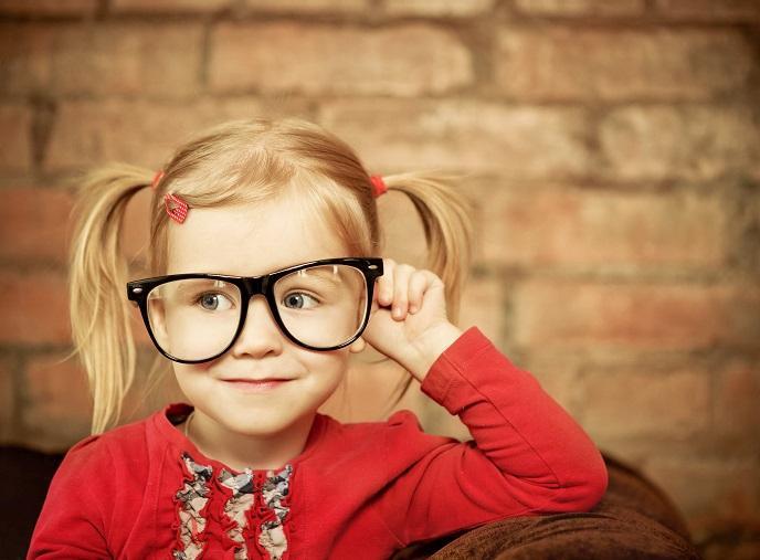 Niña rubia vestida de rojo con gafas grandes