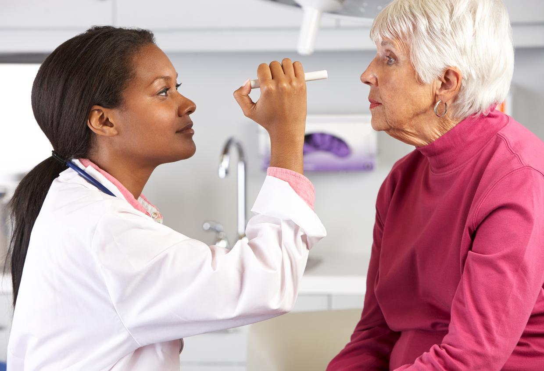 Médico revisa la vista de paciente con pelo blanco y jersey rosa