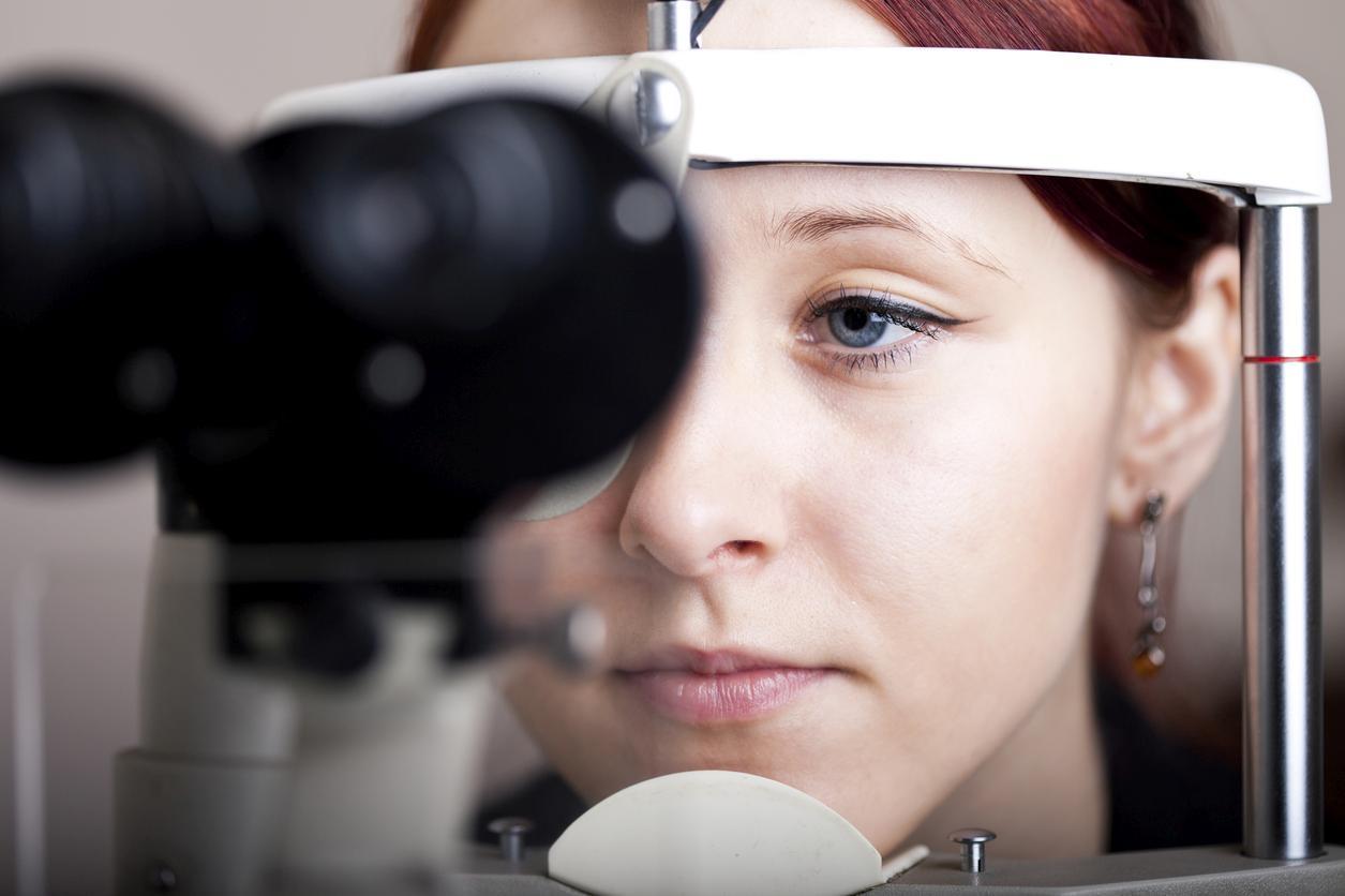 Mujer de ojos azules con grandes pendientes durante una prueba oftalmológica