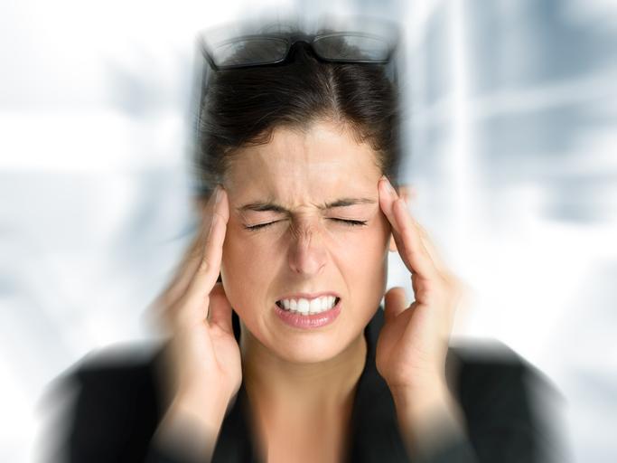 Mujer vestida de oscuro con las gafas en la cabeza frotándose las sienes