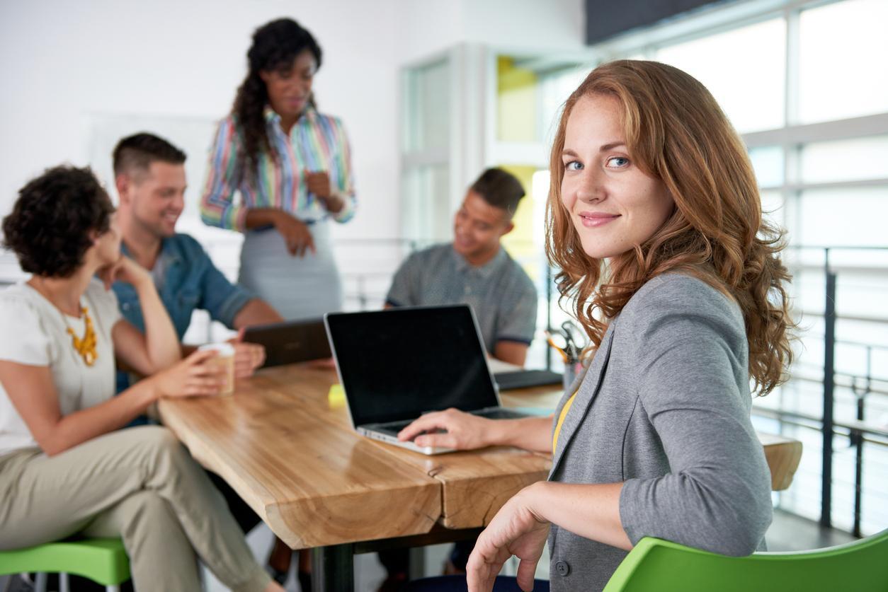 Mujer pelirroja mira a la cámara mientras está en una reunión