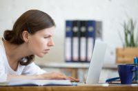 Mujer morena se acerca a la pantalla del ordenador para leer