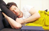 Hombre tumbado en sofá tapado con manta amarilla