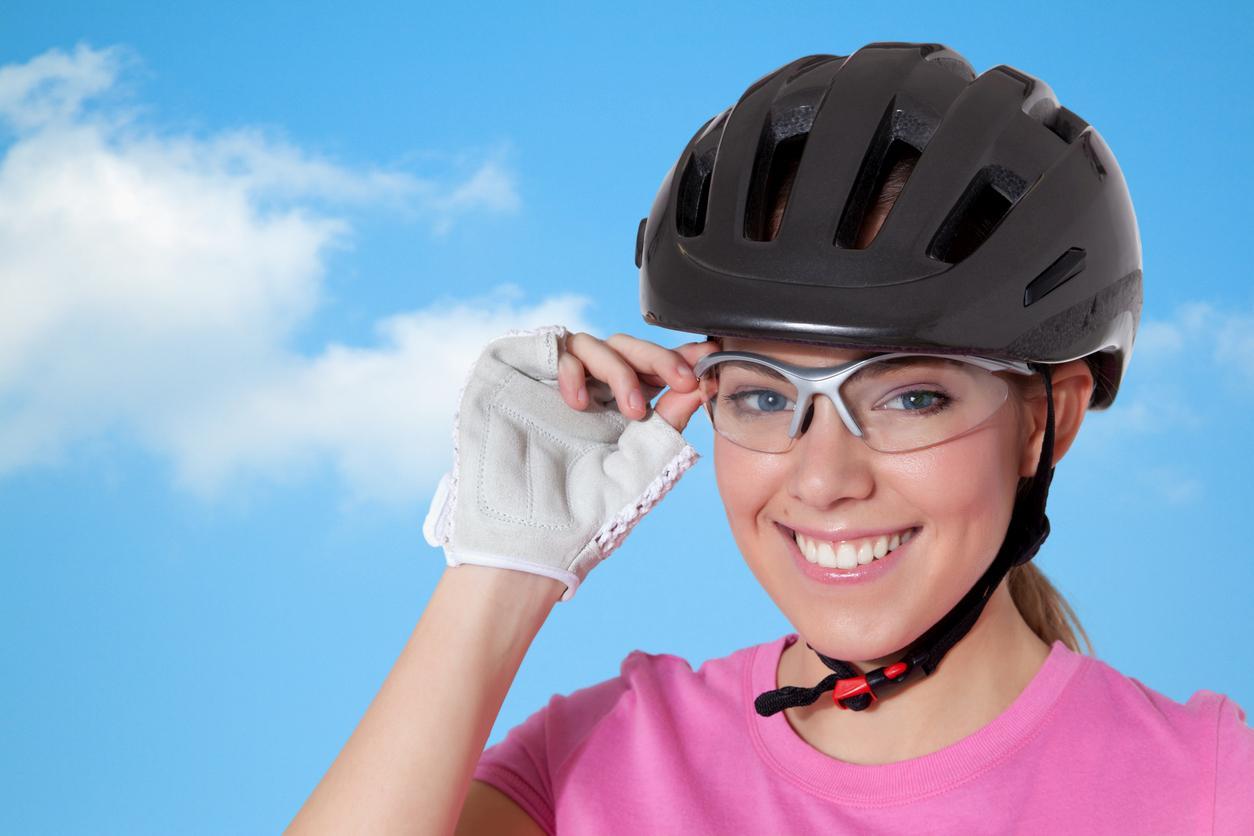 Mujer ciclista con casco, gafas y guantes