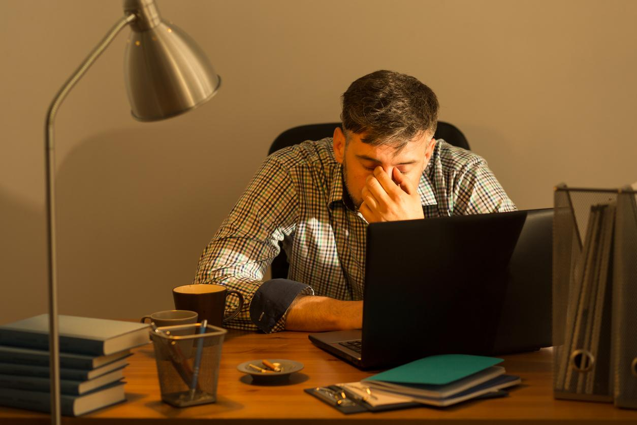 Hombre con camisa a cuadros se frota los ojos mientras trabaja con un ordenador