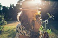 Mujer morena con gorro oliendo una flor
