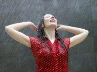 Mujer morena con camisa roja bajo la lluvia